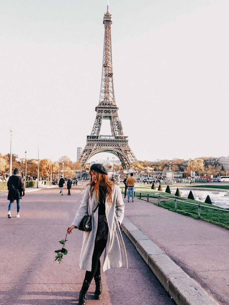 A lady holding a rose in front of the Eiffel Tower, one of the best places to visit on a romantic weekend to Paris