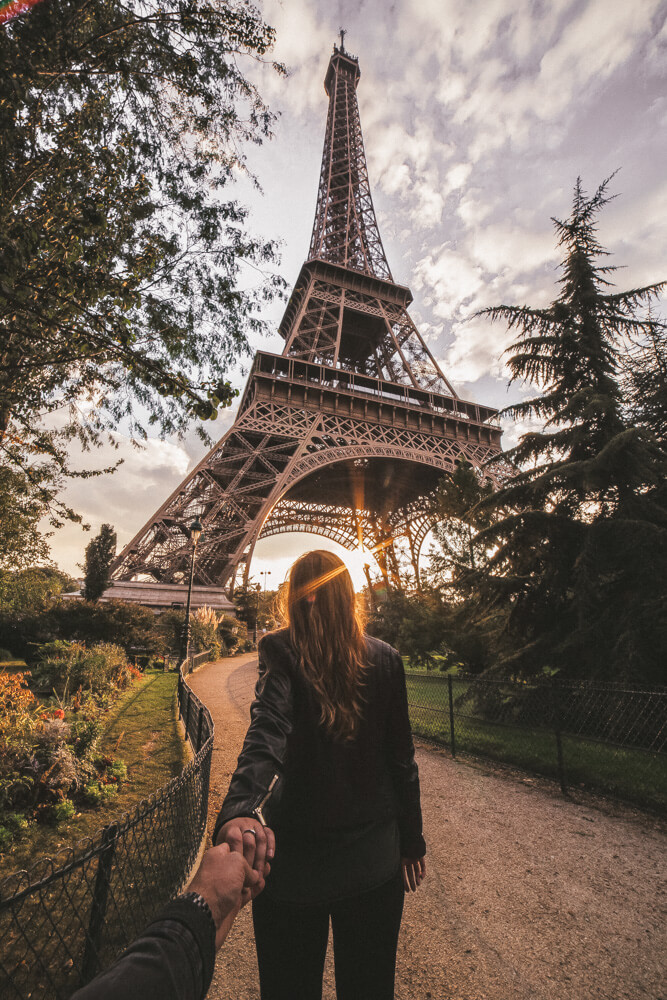 Person walking towards the Eiffel Tower at sunset, one of the best places to visit on a romantic weekend in Paris