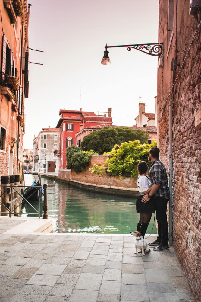 Two people leaning against a wall with a background of one of Venice's many canals