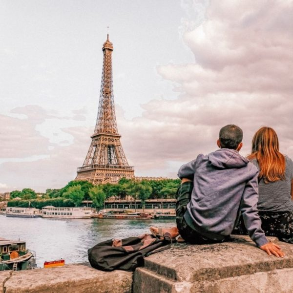 A couple sitting on the bridge overlooking the Eiffel Tower